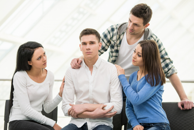 group of friends comforting young man